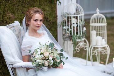 Braut im Sessel mit Brautstrauß und Blumenkäfig Fotowand