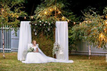 Braut im Sessel mit Brautstrauß und Blumenkäfig Fotowand Moos Lichterkette