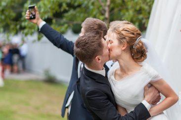 Selfie mit küssendem Brautpaar